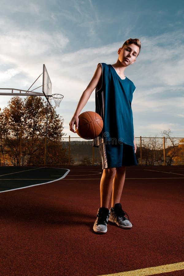 Sport et basket-ball Un jeune adolescent en maillot noir pose avec un ballon de basket sur la Playground Verticale photos stock