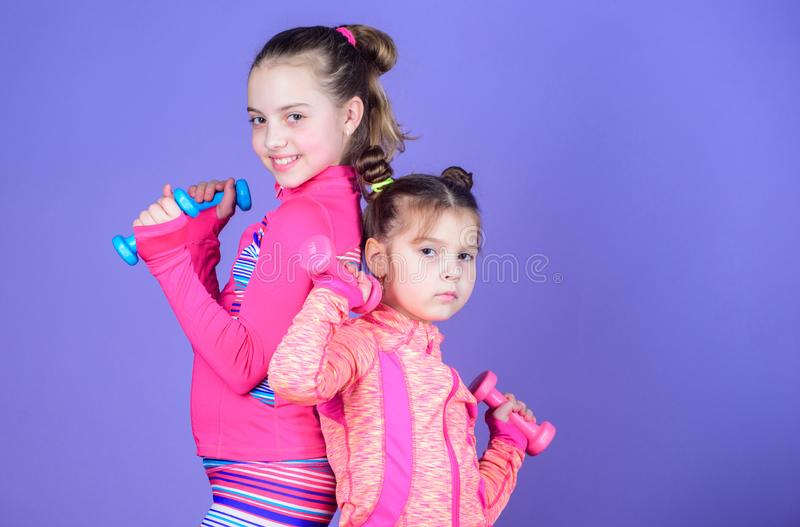Sport exercises for kids. Healthy upbringing. Sporty babies. Following her sister. Girls cute kid exercising with. Dumbbells. Motivation and sport example royalty free stock photography