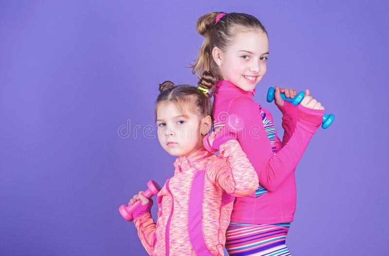 Sport exercises for kids. Healthy upbringing. Sporty babies. Following her sister. Girls cute kid exercising with. Dumbbells. Motivation and sport example royalty free stock photo