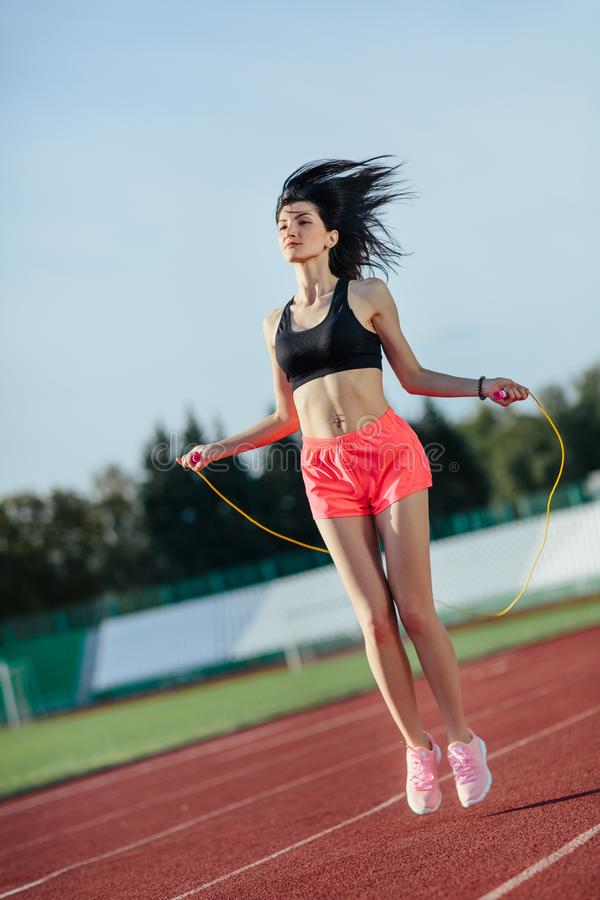 Sport, exercises outdoors. Brunette woman in black top and rose shorts jumping on skipping rope on stadium. Sporty girl in good royalty free stock images
