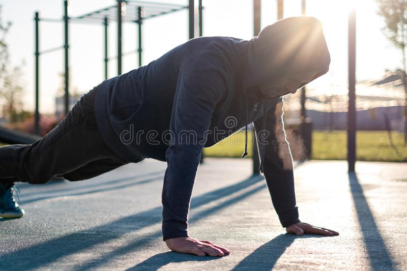 Sport, exercising, training concept. Young man doing push ups or plank exercise stock photos