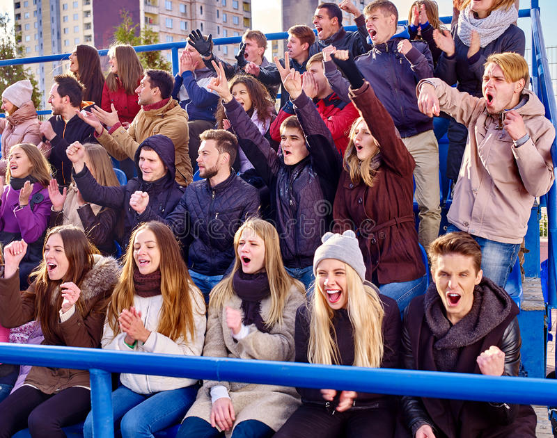 Sport fans clapping and singing on tribunes. Sport fans clapping and crying on tribunes. Group adult people stock image