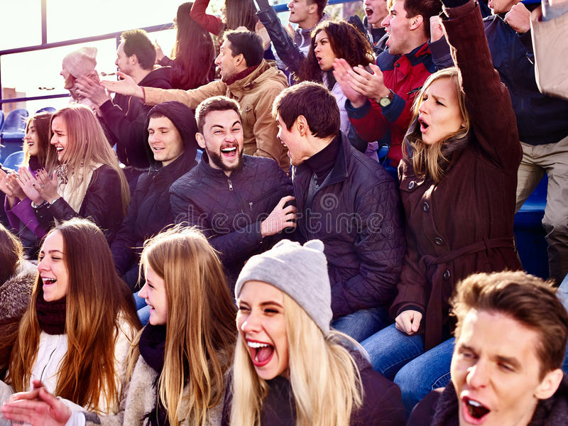 Sport fans clapping and singing on tribunes. Emotion sport fans clapping and singing on tribunes. Group people stock photo