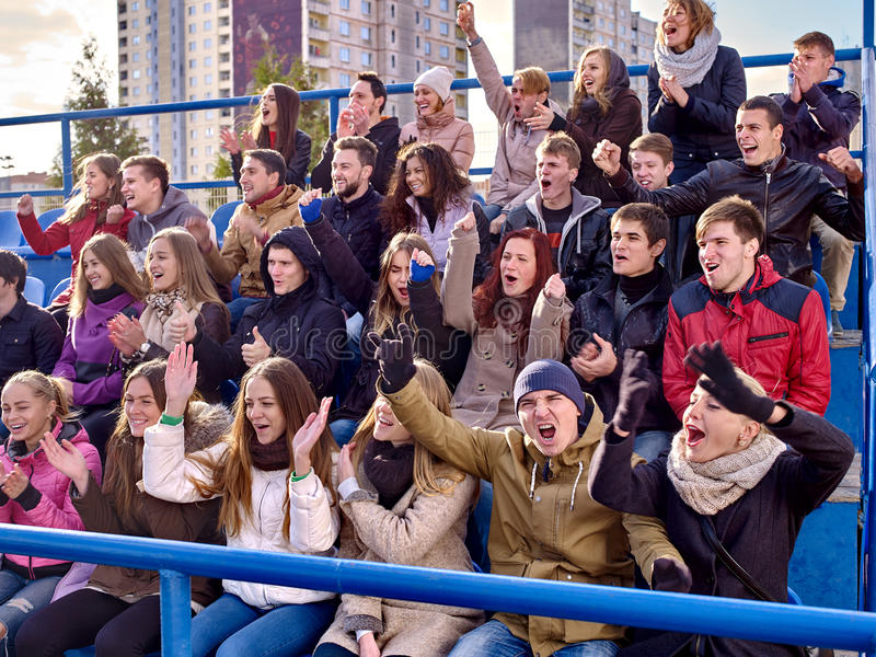 Sport fans clapping and singing on tribunes. Group emotion people stock images