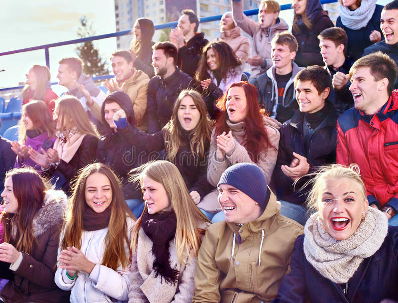Sport fans clapping and singing on tribunes. Group happy young people stock photo