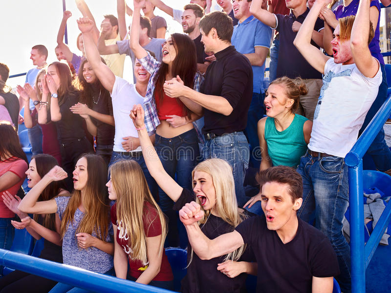 Sport fans clapping and singing on tribunes. Group people of sport fans stock photography