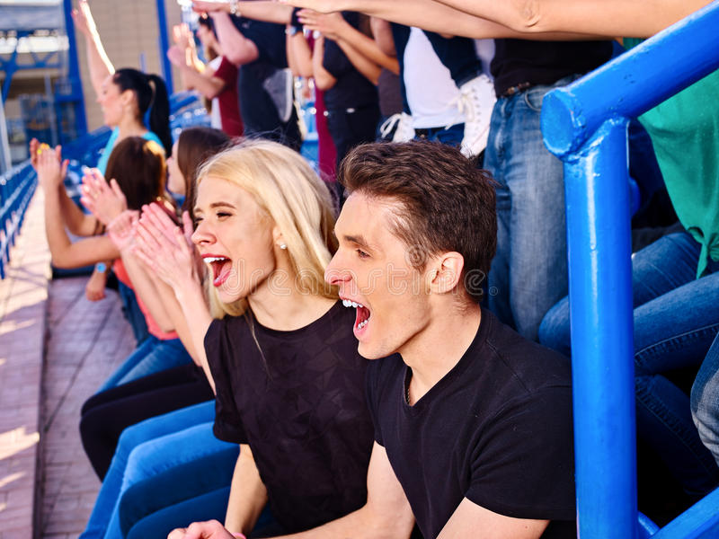 Sport fans clapping and singing on tribunes. Group people. Couple on foreground royalty free stock images