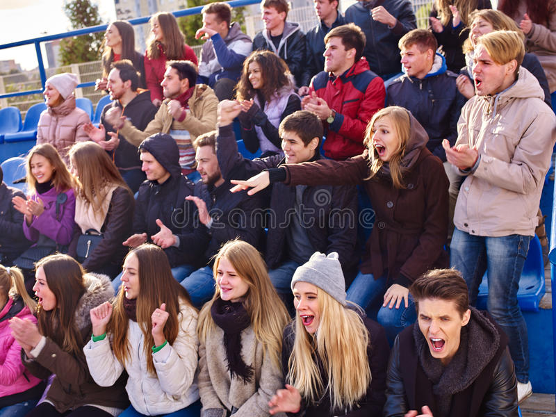 Sport fans clapping and singing on tribunes. Group young people wearing winter clothers stock images
