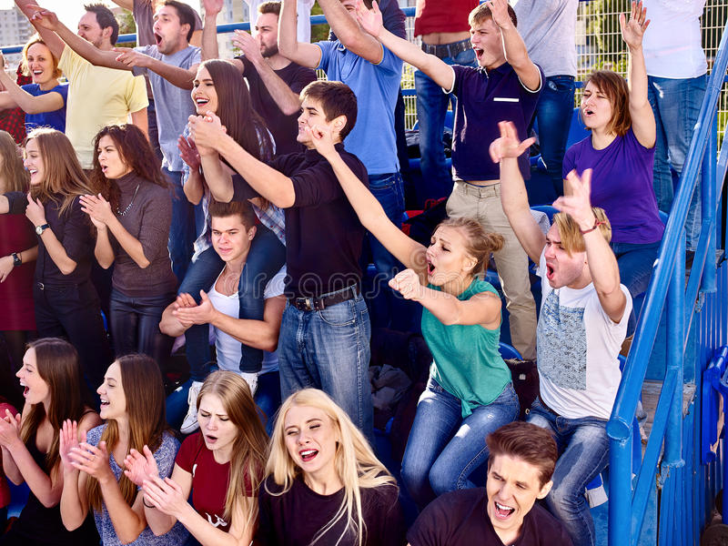 Sport fans clapping and singing on tribunes. Sport fans clapping hand up and singing on tribunes. Group people stock photo