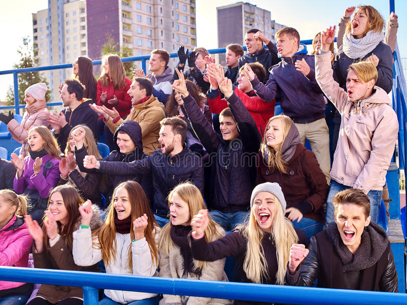 Sport fans clapping and singing on tribunes. Sport fans hands up clapping and singing on tribunes. Group people stock photos