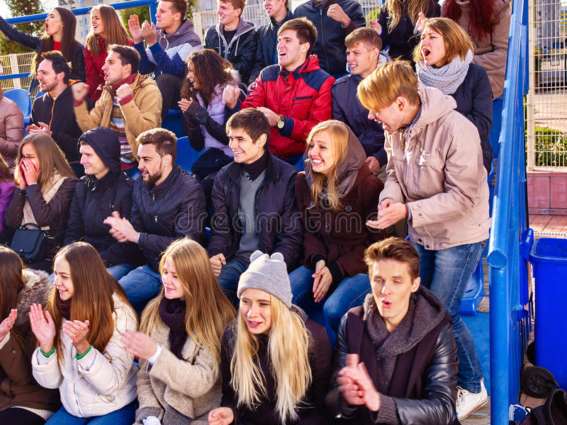 Sport fans clapping and singing on tribunes. Large group of sport fans clapping and singing on tribunes stock photos