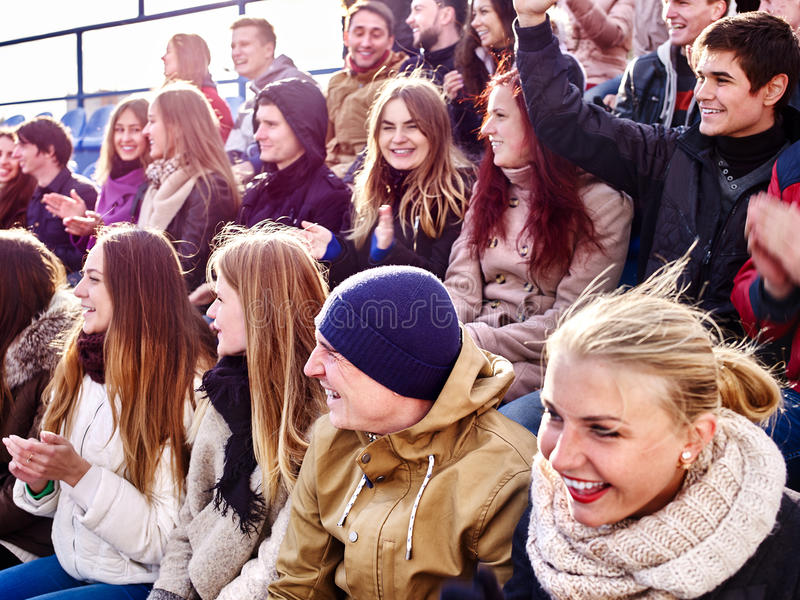 Sport fans clapping and singing on tribunes. Sport fans large group clapping and singing on tribunes. Group people royalty free stock photo