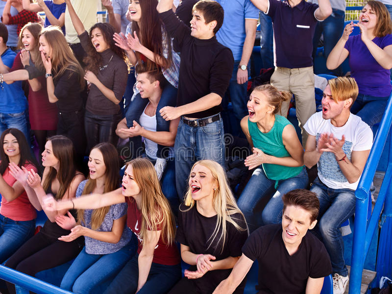 Sport fans clapping and singing on tribunes. Large group sport fans clapping and singing on tribunes. Group people royalty free stock photo