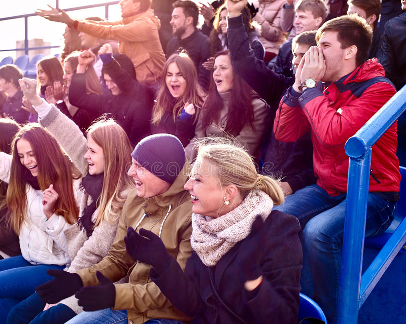 Sport fans clapping and singing on tribunes. Sport fans wearing hat and scarf clapping and singing on tribunes. Group people royalty free stock photos