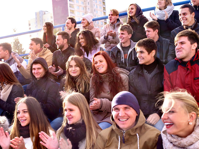Sport fans clapping and singing on tribunes. Winter weather. Sport fans clapping and singing on tribunes. Large group people and winter cool weather stock photo
