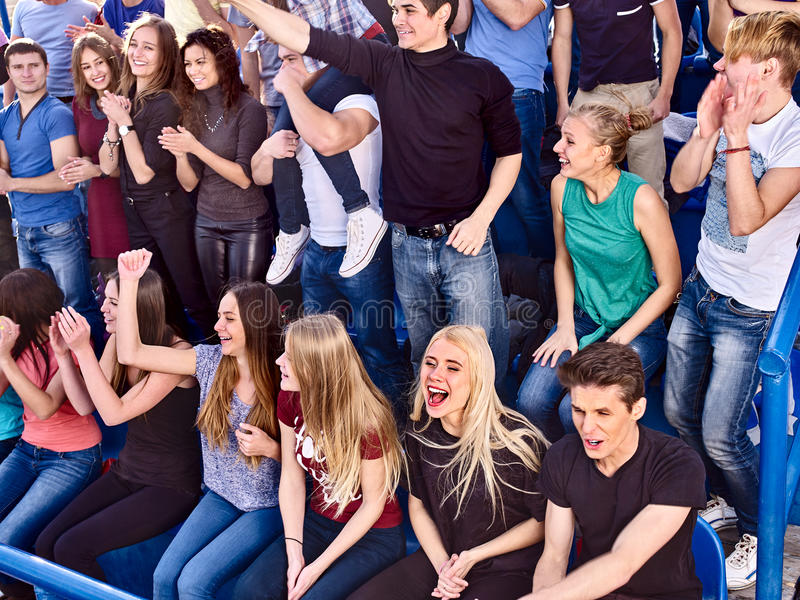 Sport fans clapping and singing on tribunes. Sport young fans boy and girl clapping and singing on tribunes. Group people royalty free stock photos