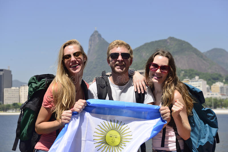 Sport fans friends in Rio de Janeiro holding Argentinian flag. Group of backpackers sport fans traveling at Rio de Janeiro holding Argentinian flag, with Christ royalty free stock photos