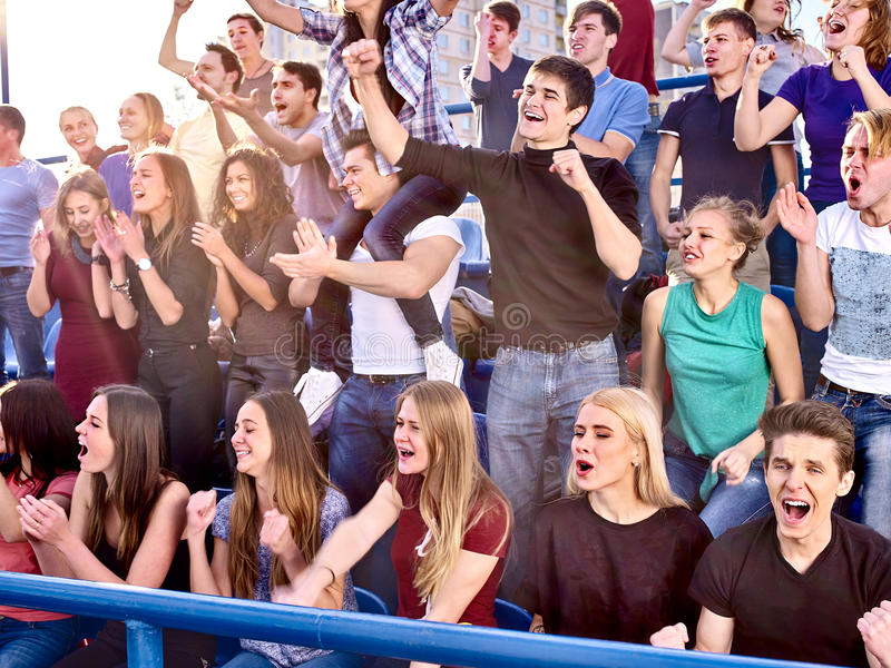Sport fans hands up and singing on tribunes. Sport football fans hands up and singing on tribunes. Group football fans people royalty free stock photo