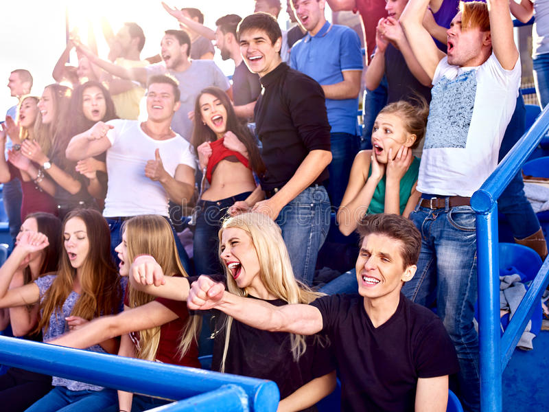 Sport fans hands up and singing on tribunes. Group sport fans people on foreground royalty free stock image