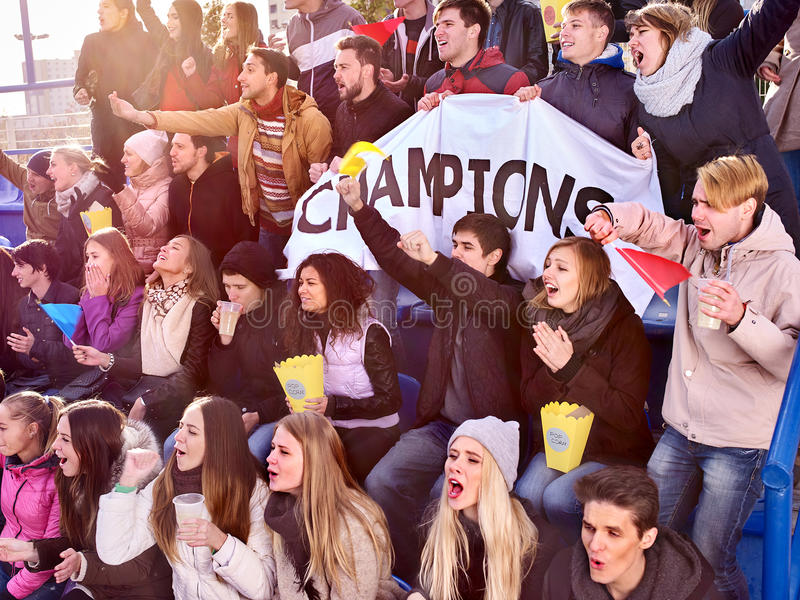 Sport fans holding champion banner on tribunes. Sport fans holding champion banner and eating popcorn on tribunes. Group people royalty free stock photography