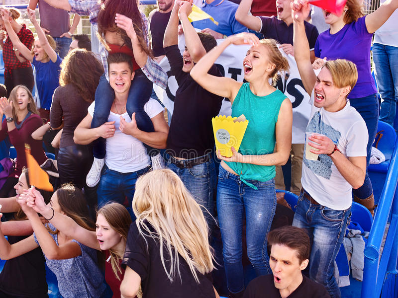 Sport fans holding champion banner on tribunes. Sport fans eating popcorn and singing on tribunes. Group emotion people stock photography
