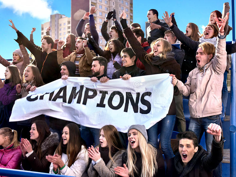 Sport fans holding champion banner on tribunes. Sport fans holding champion banner and singing on tribunes. Group people stock images