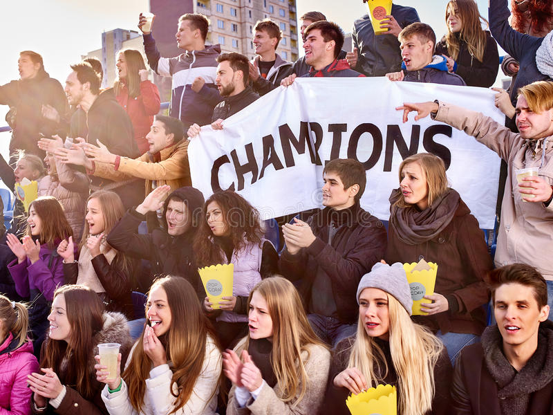 Sport fans holding champion banner on tribunes. Sport fans in warm clothers holding champion banner and singing on tribunes. Group people stock images