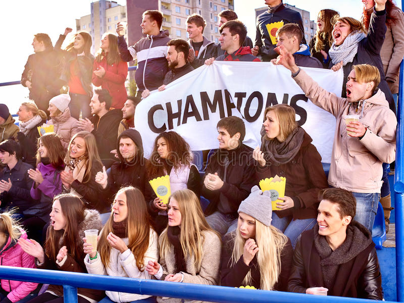 Sport fans holding champion banner on tribunes. Sport fans holding banner with writting champion and singing on tribunes. Group people royalty free stock photo