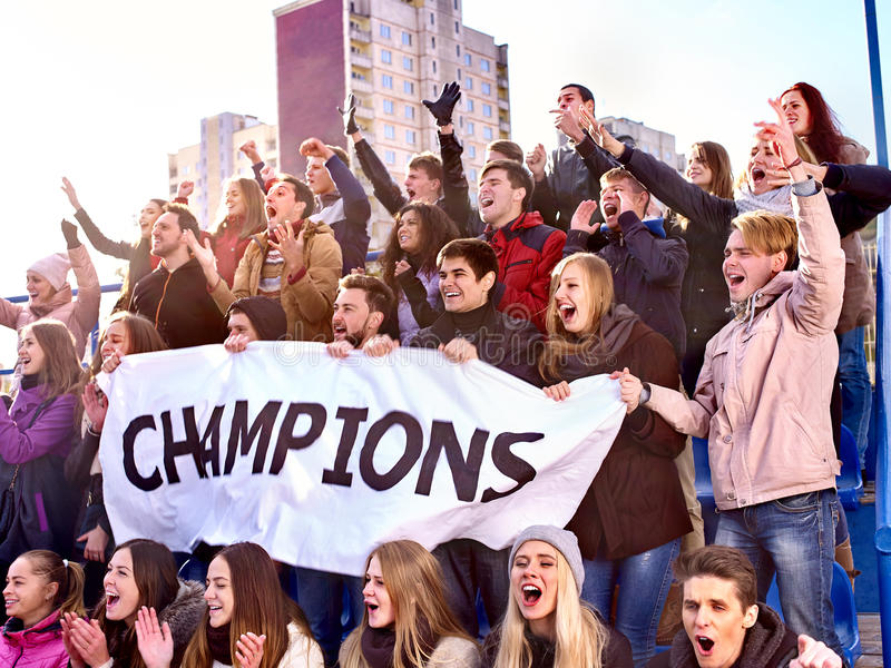 Sport fans keep champion banner on tribunes. Sport fans keep champion banner and singing on tribunes. Group people hands up royalty free stock images