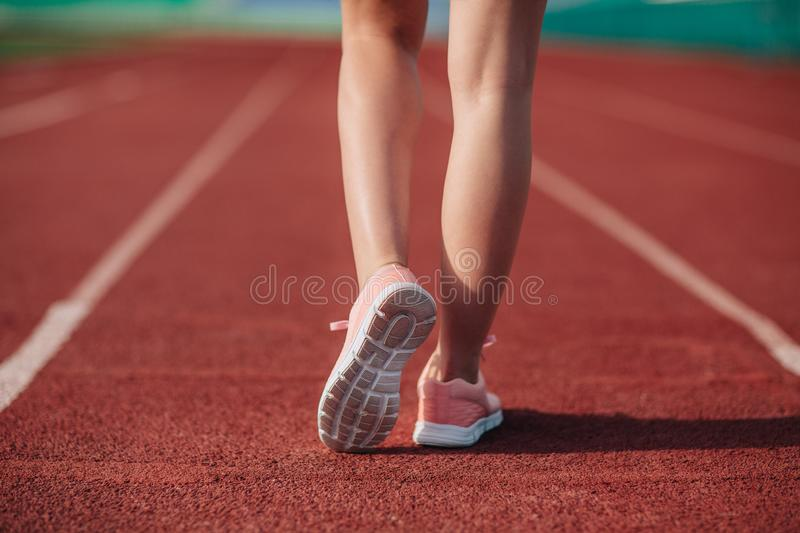Sport. Female legs in pink sneakers on running track stadium. Close-up on sports shoes of a running woman. Concept run.  stock photos