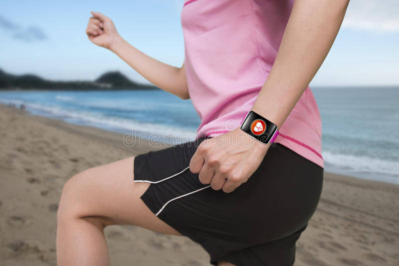 Sport female wearing bright pink watchband bent touchscreen smartwatch. With red health icon on natural sea beach background stock photos