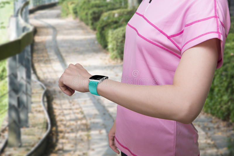 Sport female wearing smartwatch with blank black glass bent touchscreen. On natural tree background royalty free stock images