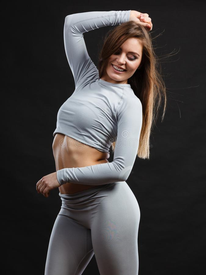 Sport fit woman in thermal clothes. Sporty fitness shape garments concept. Attractive lady in thermal clothes. Young seductive girl pulling shirt showing skin stock photos