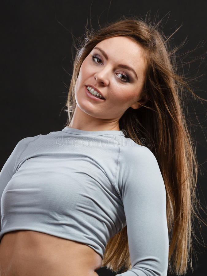 Sport fit woman in thermal clothes. Sporty fitness shape garments concept. Attractive lady in thermal clothes. Young seductive girl pulling shirt showing skin royalty free stock photography