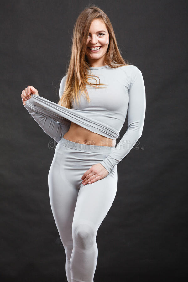 Sport fit woman in thermal clothes. Sporty fitness shape garments concept. Attractive lady in thermal clothes. Young seductive girl pulling shirt showing skin stock photography