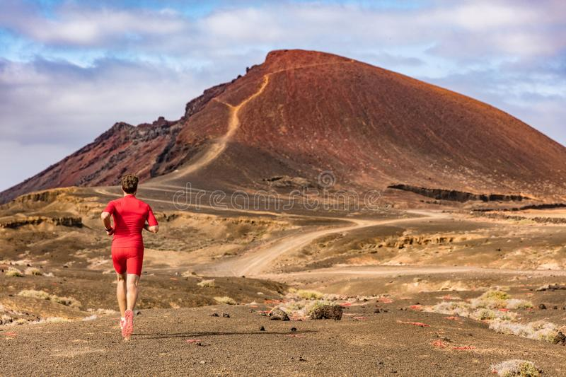 Sport and fitness athlete running on mountain trail, man active lifestyle. Man runner on long distance run through desert summer royalty free stock images