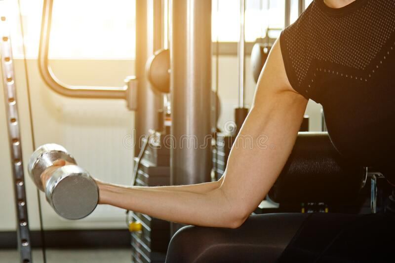 Sport, fitness, bodybuilding, weightlifting and people concept - close up of woman flexing arms with dumbbell in gym royalty free stock images