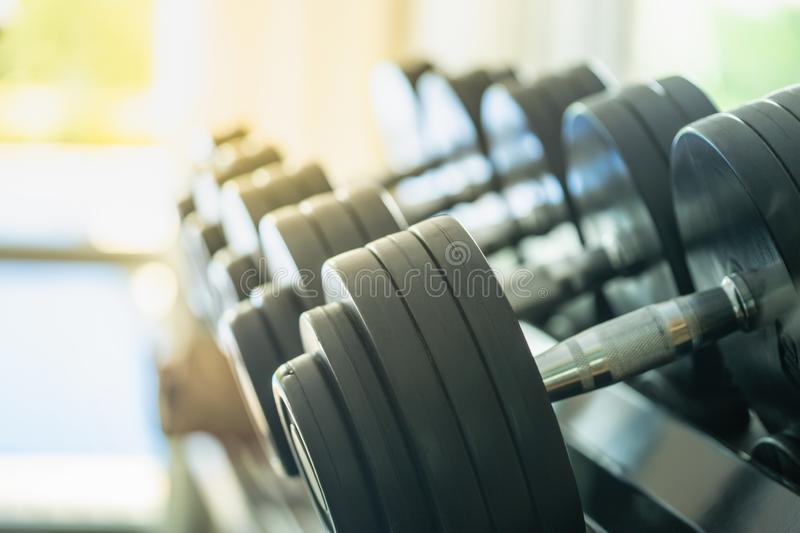 Sport and Fitness Concept. Rows of metal dumbbells on rack in the gym / sport club with copy space. Weight Training Equipment stock photo
