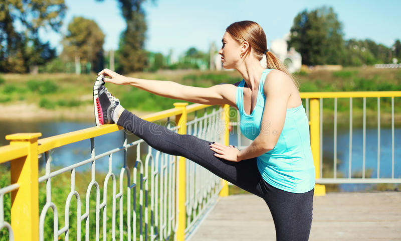 Sport and fitness concept - woman doing stretching exercise in city stock photography