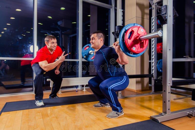 Sport, fitness, groepswerk, bodybuilding mensenconcept - mens en persoonlijke trainer met de spieren van de barbellverbuiging in  royalty-vrije stock fotografie