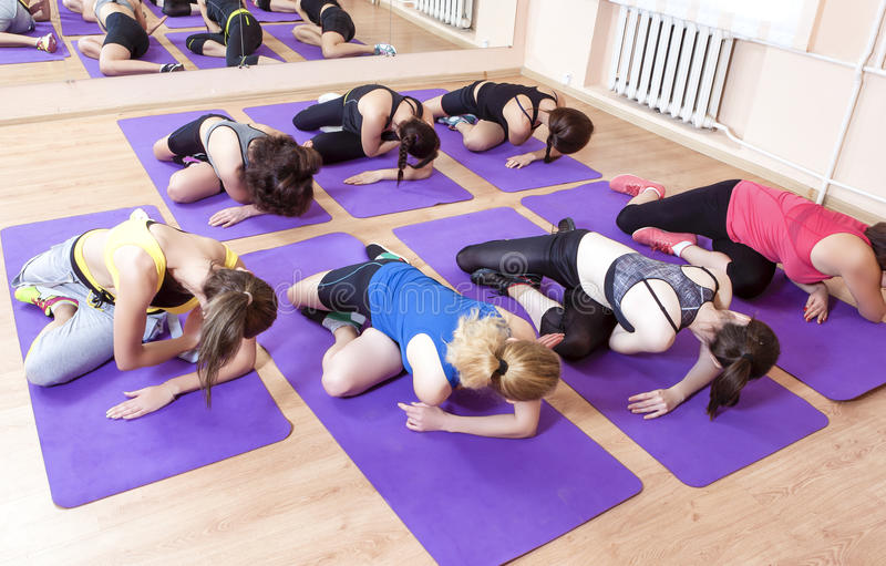 Sport, Fitness, Healthy Lifestyle Concepts. Group of Caucasian Women Having Stretching Workout. Indoors on Purple Sport Mats. Horizontal Image Composition royalty free stock images