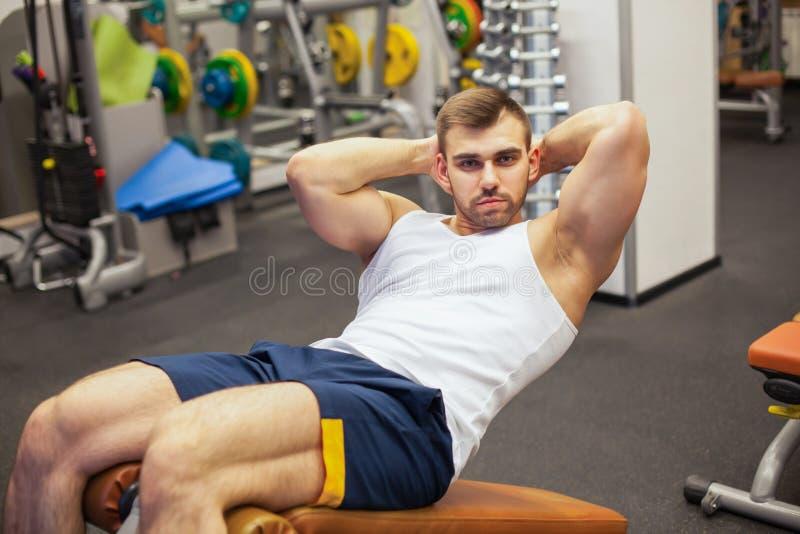 Sport, fitness, het bodybuilding, levensstijl en mensenconcept - jonge mens die zitten-op de buikpers van de oefeningenbank binne stock foto