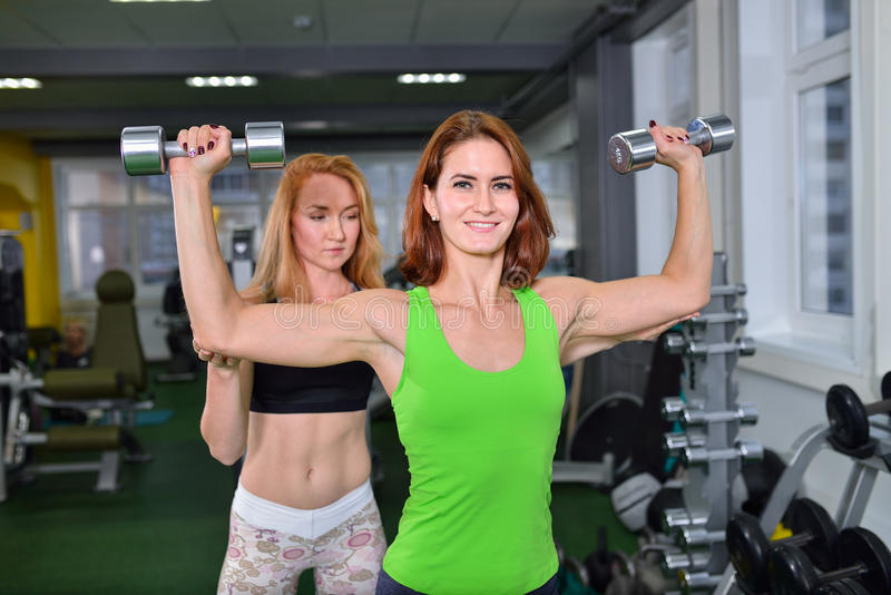 Sport, fitness, lifestyle concept - Woman doing chest and shoulder dumbbell press with personal coach assisting her stock images