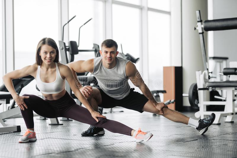 Sport, fitness, lifestyle and people concept - smiling man and woman stretching in gym royalty free stock image
