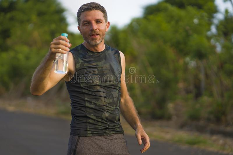 Sport and fitness lifestyle portrait of young attractive and happy man drinking water tired and exhausted after hard outdoors. Running workout on beautiful stock images