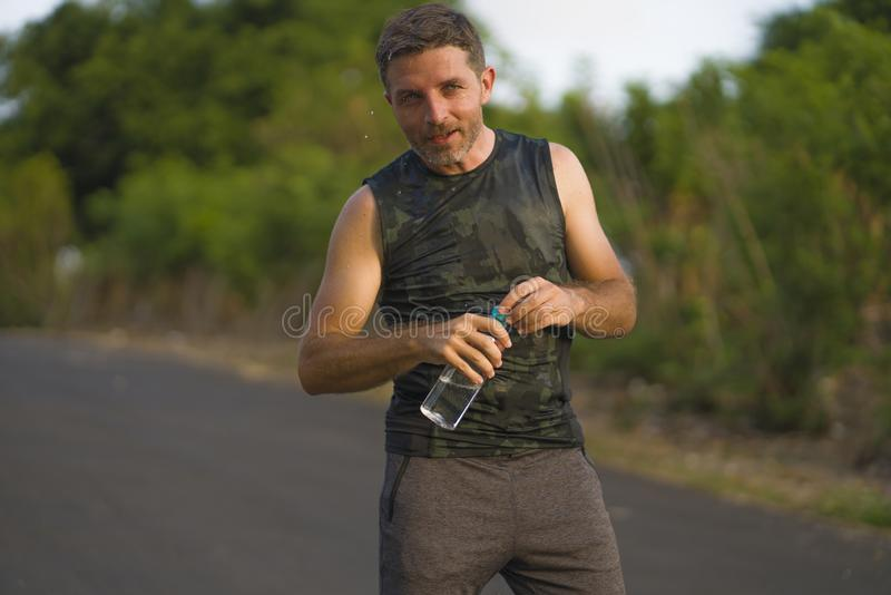Sport and fitness lifestyle portrait of young attractive and happy man drinking water tired and exhausted after hard outdoors. Running workout on beautiful royalty free stock photos