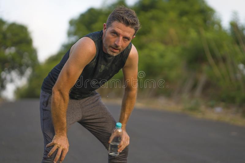 Sport and fitness lifestyle portrait of young attractive sweaty and tired man exhausted after outdoors running workout on. Beautiful country road breathing stock images