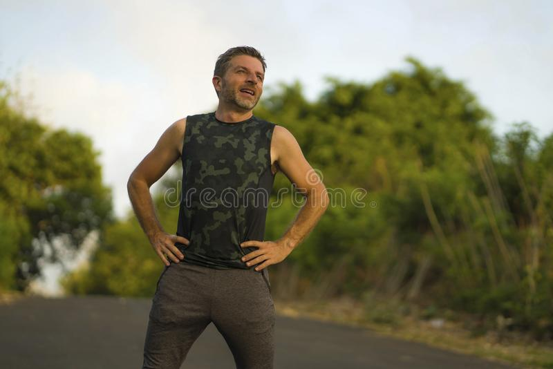 Sport and fitness lifestyle portrait of young attractive sweaty and tired man exhausted after outdoors running workout on. Beautiful country road breathing stock photography