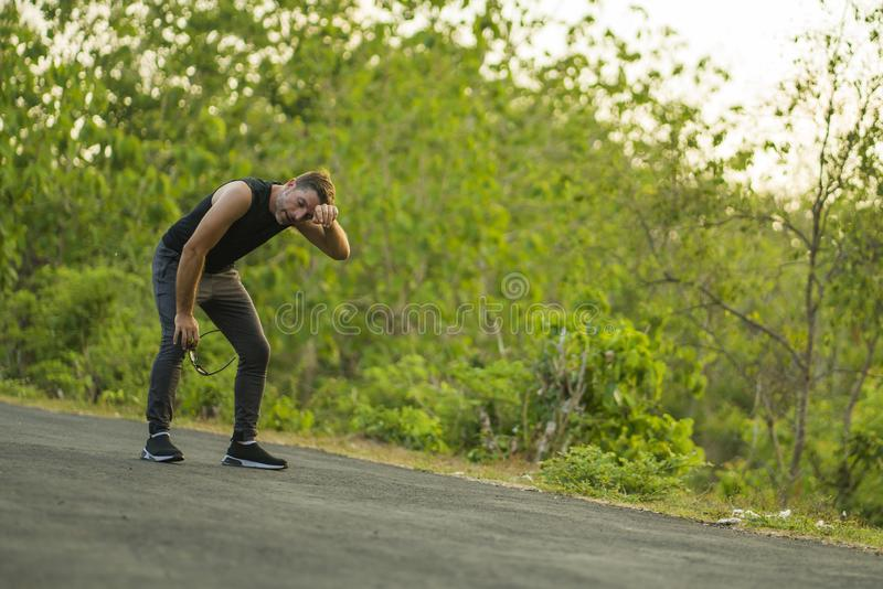 Sport and fitness lifestyle portrait of young attractive sweaty and tired man exhausted after outdoors running workout on. Beautiful country road breathing royalty free stock photo
