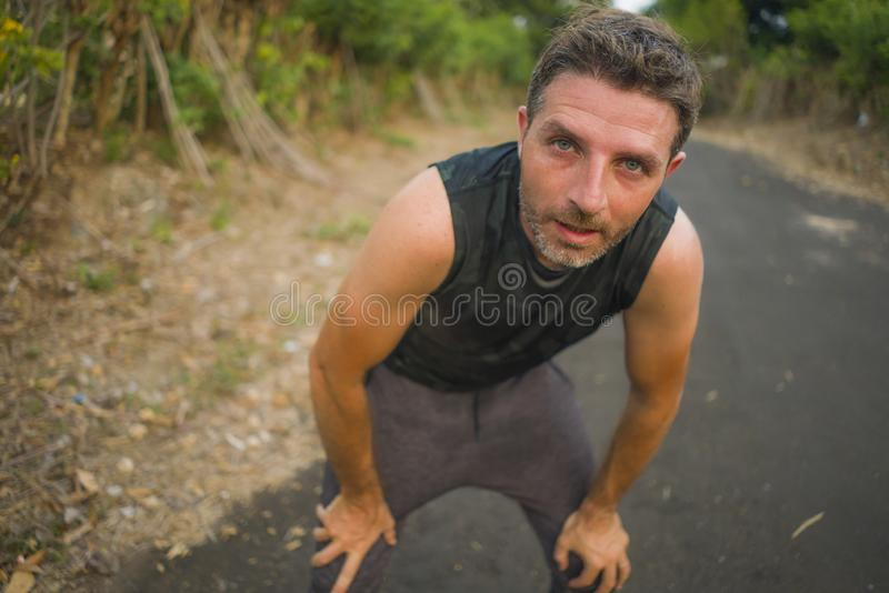 Sport and fitness lifestyle portrait of young attractive sweaty and tired man exhausted after outdoors running workout on royalty free stock images